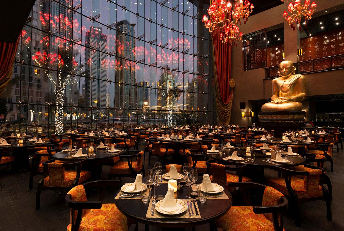 The interior of the Buddha Bar restaurant in Dubai with a tall Buddha sculpture overlooking the dining tables and floor-to-window ceilings overlooking the glamorous Dubai Marina