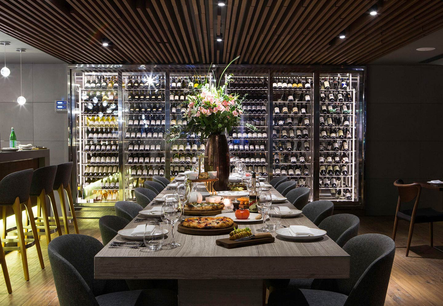 The interior of Marina Social restaurant in Dubai Marina with a long dining table, a beautiful flower arrangement and stacks of bottled grape