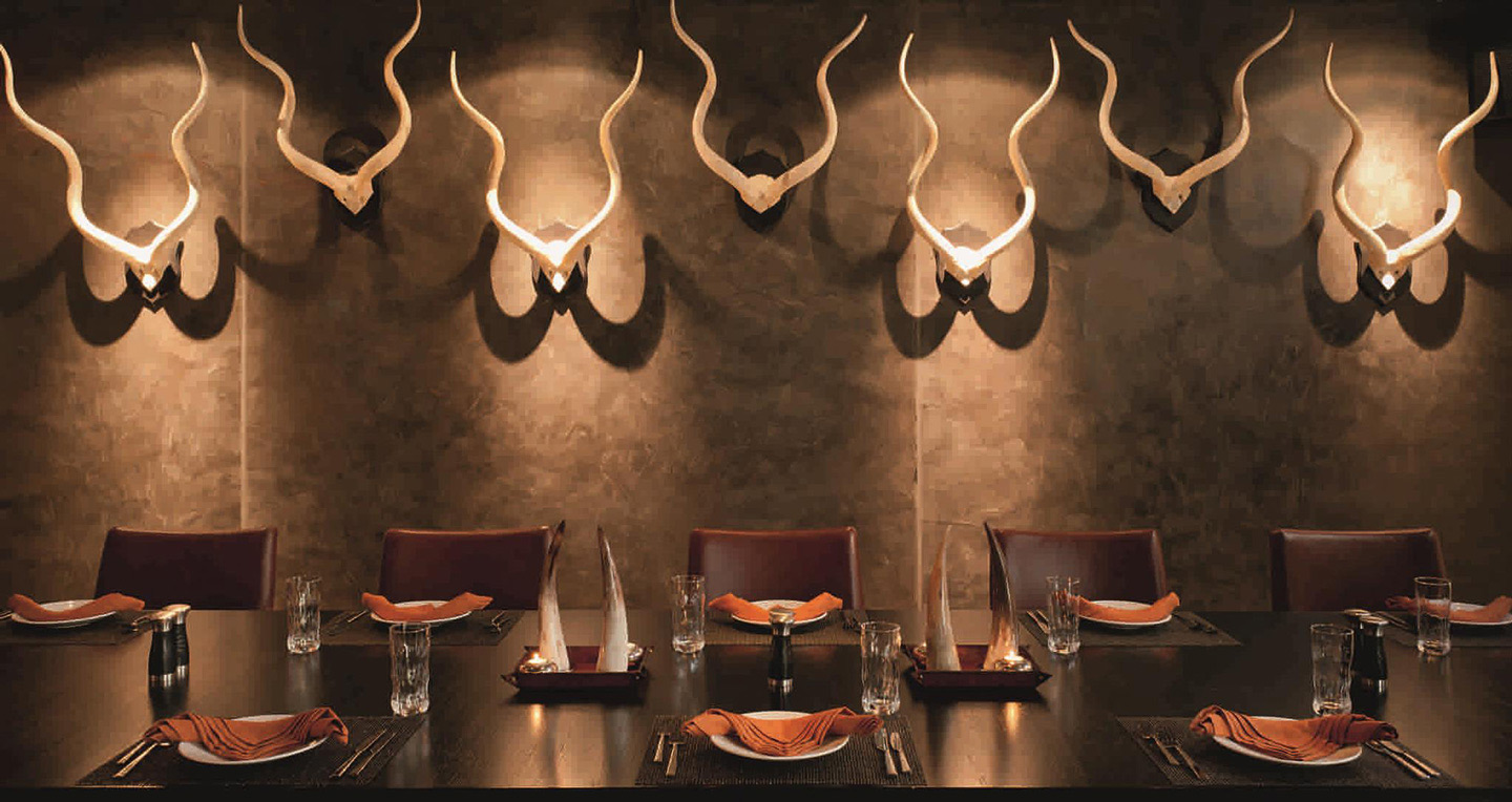 The chocolate coloured interior of Toro Toro Dubai with an exquisite table setting and creative bull horn motifs on the wall