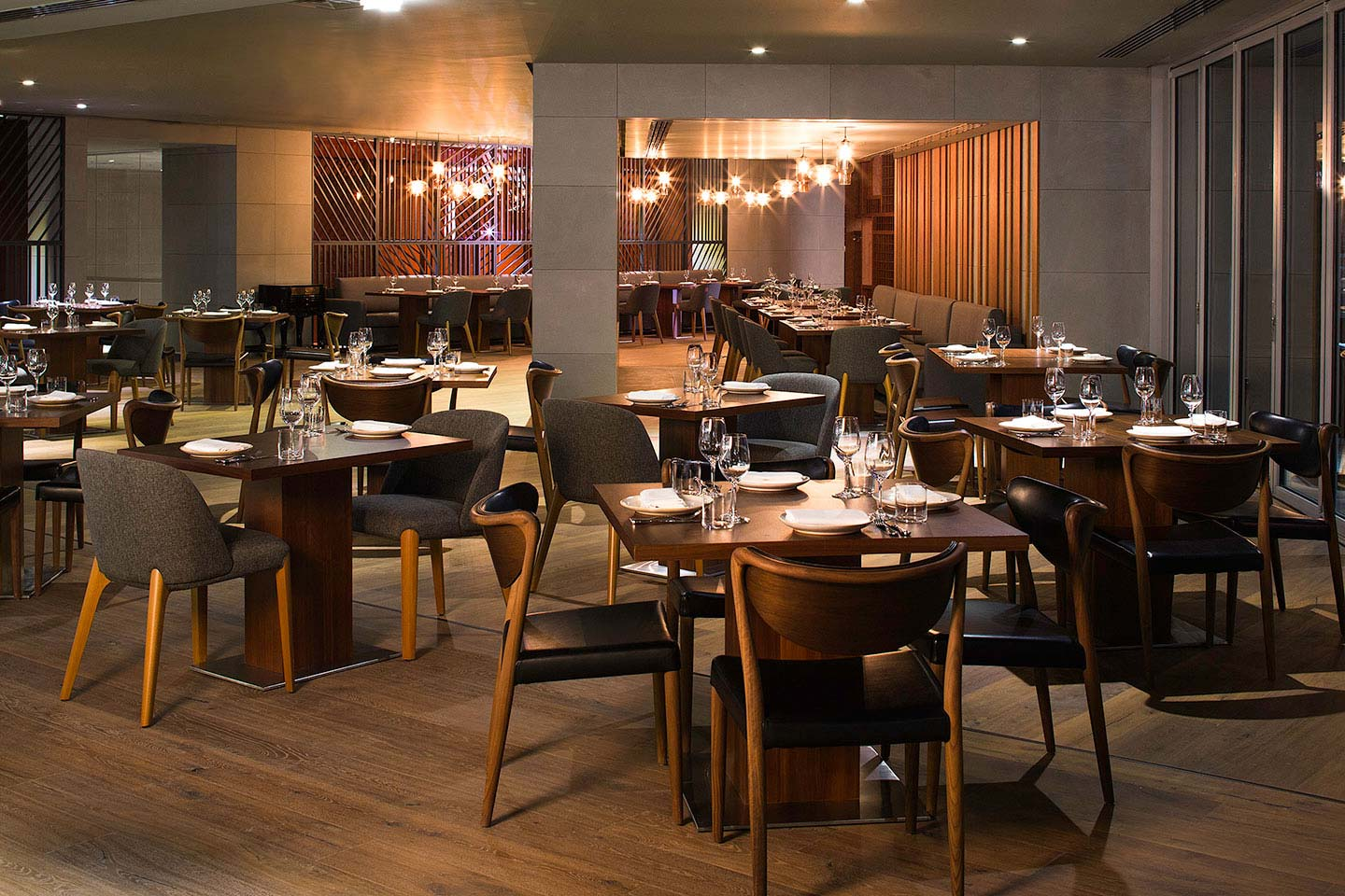 The interior of Marina Social with nicely laid out dining tables and intimate lighting