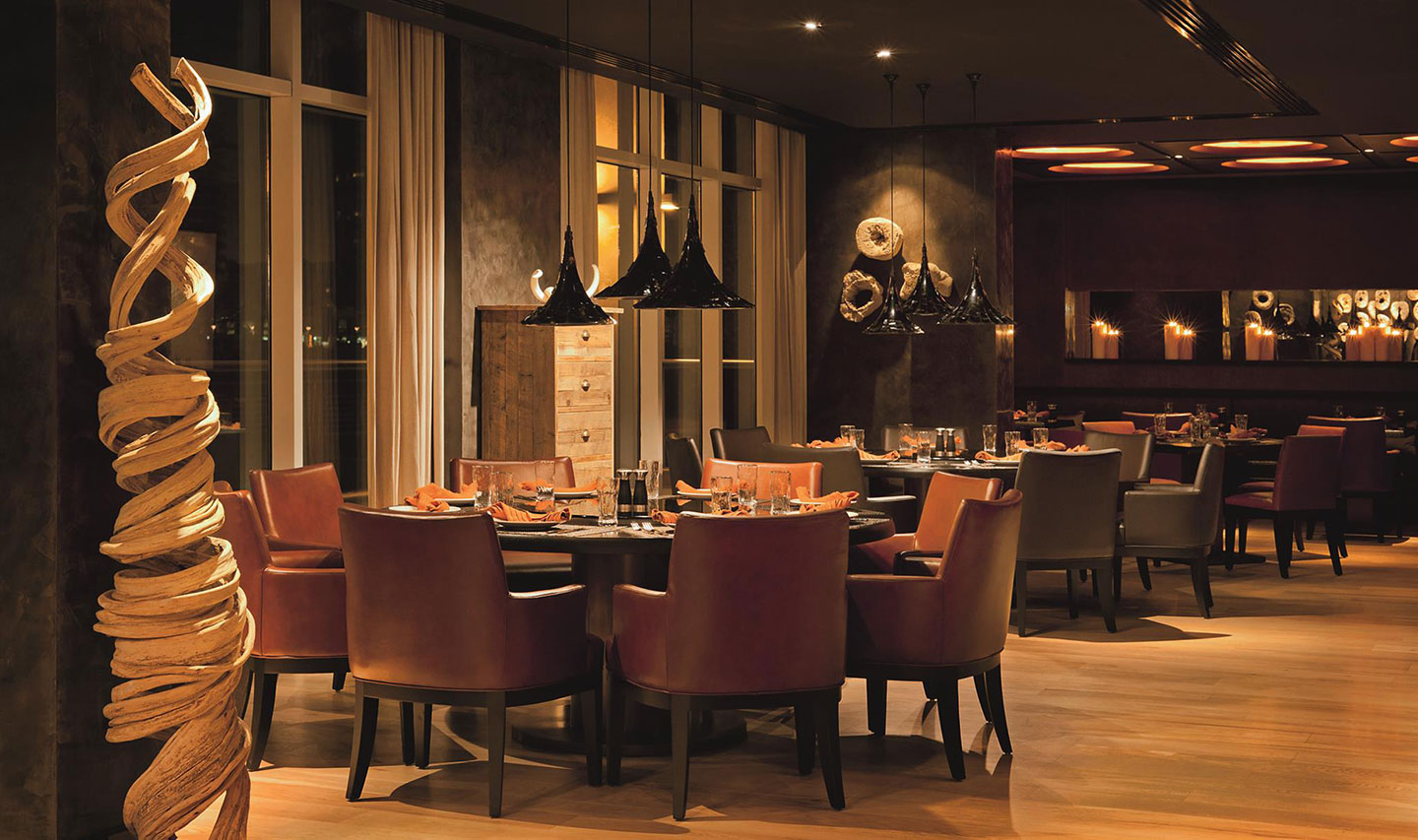 The chocolate-coloured interior of Toro Toro Dubai with round dining tables and soft lighting and an intimate atmosphere