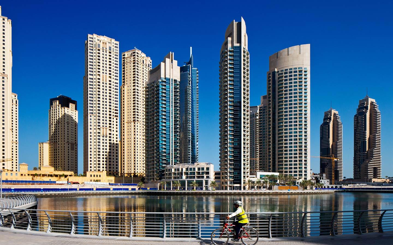 A man cycling by the Dubai Marina