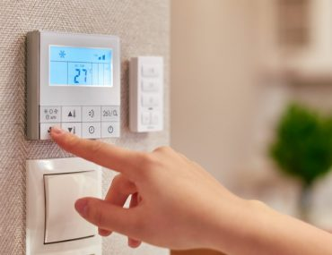 Person adjusting AC thermostat in a house, located in of the district cooling areas in Dubai