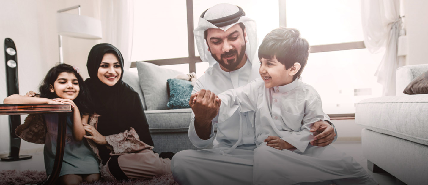 Happy Emirati family with parents and kids playing in living room