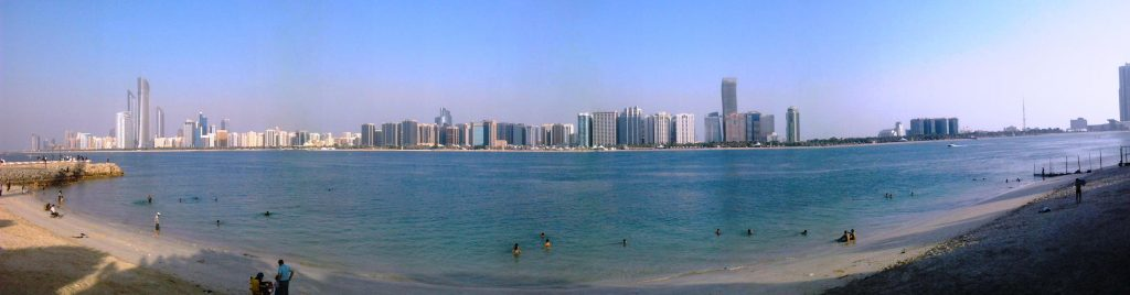 A panorama of the crystal blue waters of Abu Dhabi and the Marina Village as seen from the Corniche Beach