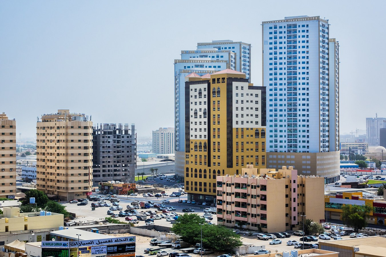 The cityscape of Ajman, UAE with both high-rise and low-rise buildings and the blue sky in the background