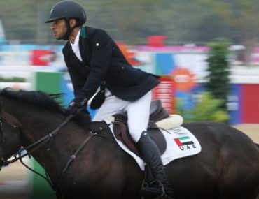 Show jumping rider on a horse at Al Ain Equestrian Shooting and Golf Club