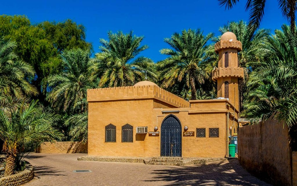 A mosque surrounded by palm trees