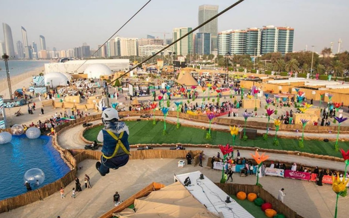 Person zip-lining at Al Bahar at Abu Dhabi Corniche, one of the outdoor attractions in Abu Dhabi