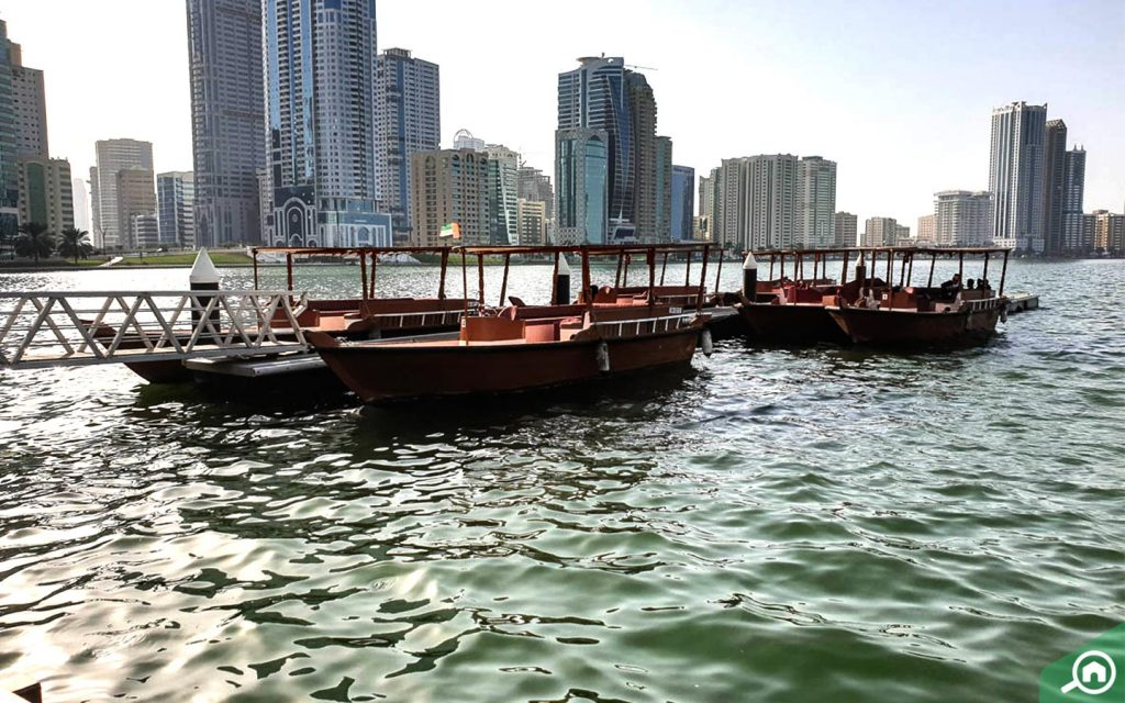 Dhow tied up on the water in Al Majaz with buildings in the background
