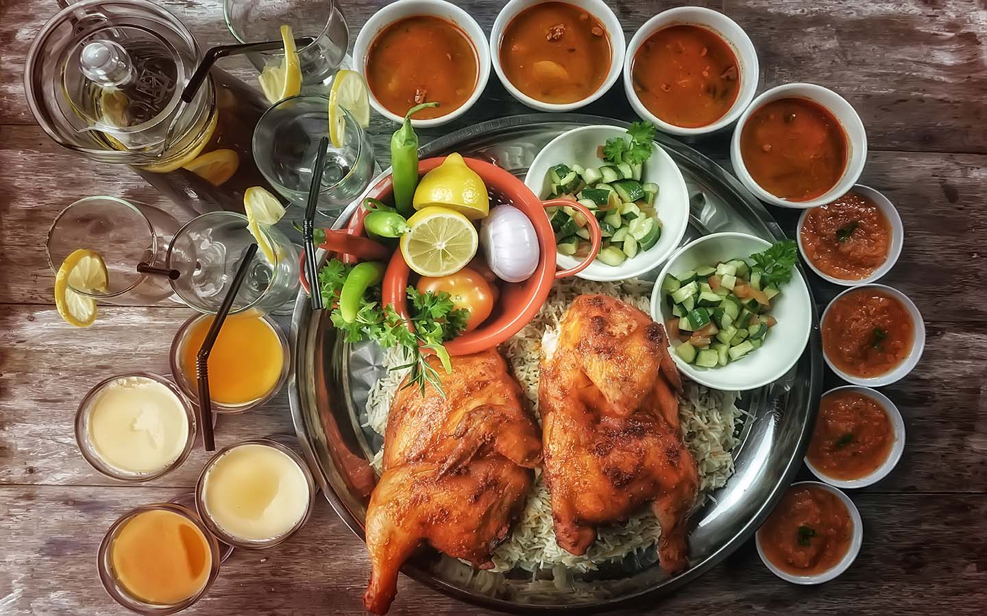 Top view of Chicken Mandy/Kabsa Rice, a kind of Arabian main course complete with side dishes and dessert.
