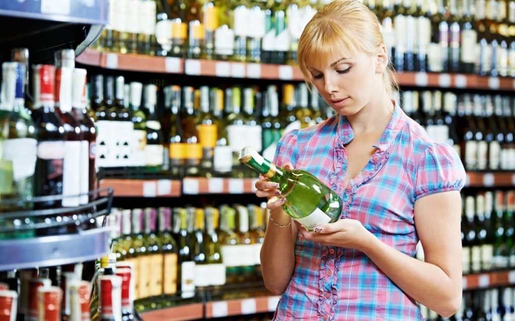 Women selecting a bottle in an alcohol shop in Ajman