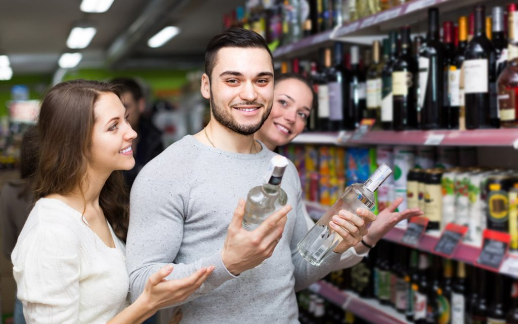 A happy group buying alcohol from a liquor store in Ajman