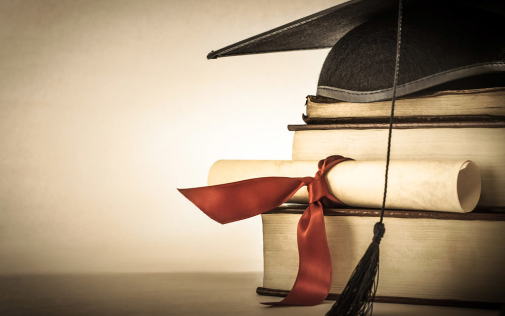 Graduation cap placed over books and degree approved by Ministry of Education UAE