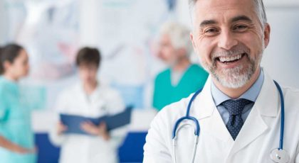 smiling middle aged male doctor with other medical professionals in the background