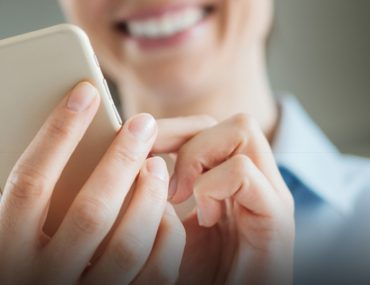 Smiling woman typing on smartphone screen