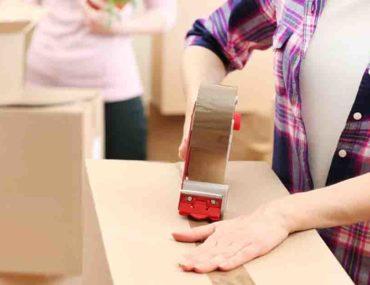 Women taping moving box