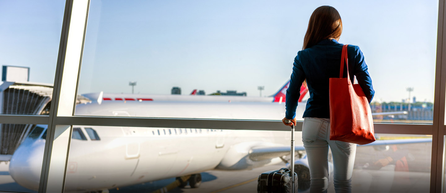 Woman with luggage waiting to board aircraft in front of her at airport