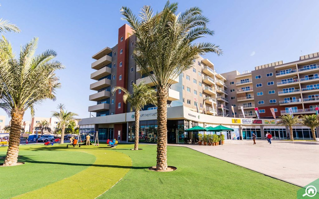 View of apartment buildings and shops in Al Reef