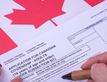 Visa application form being filled out with Canadian flag in the background