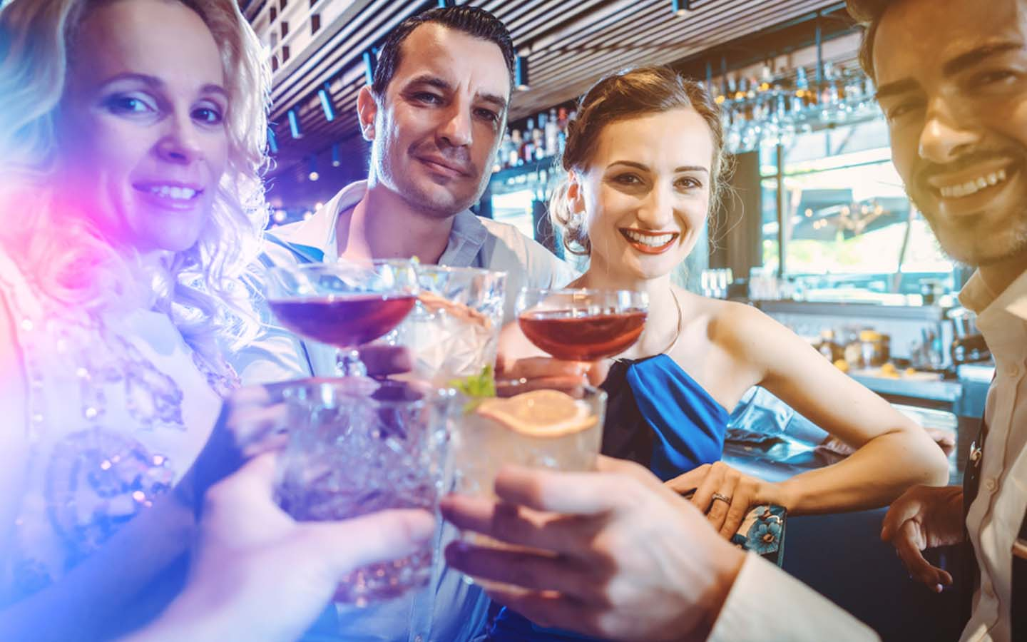 Friends at a bar in DIFC with drinks in hand