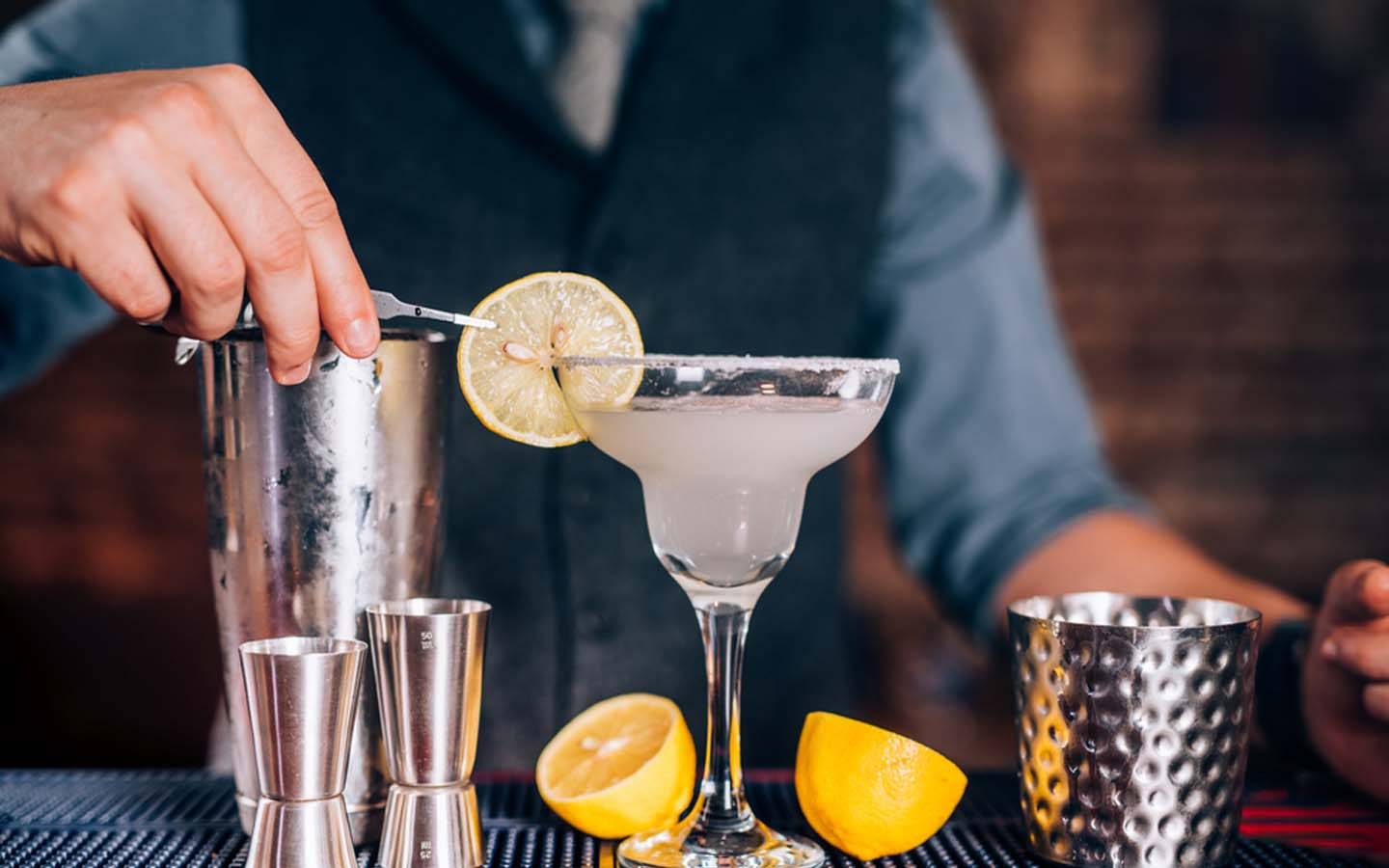 Bartender making a drink with fresh lemon, vodka and limes