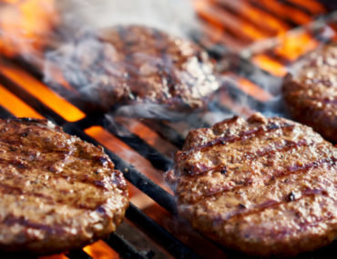 Grilling fresh patties for burgers in Ajman