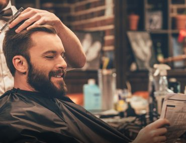 Man getting haircut and reading newspaper