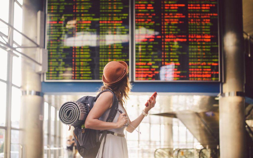 Female traveller looking at display board at airport