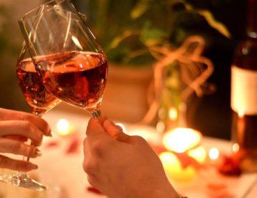 Couple clinking wine glasses in romantic restaurant