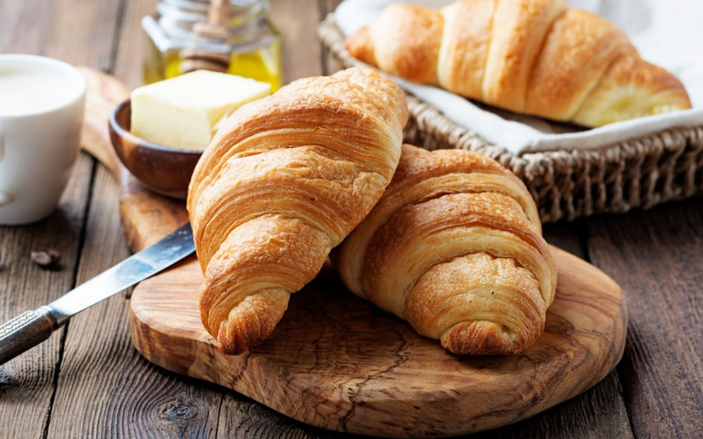 two croissants on  a bread board