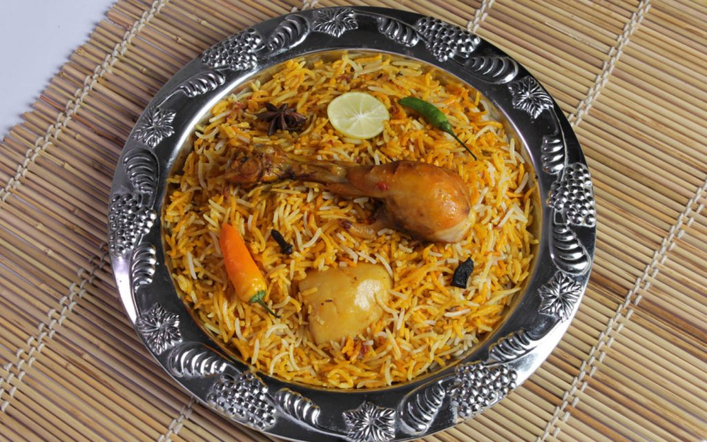 Chicken biryani in Abu Dhabi served in a traditional platter with lemon and green chili as garnish