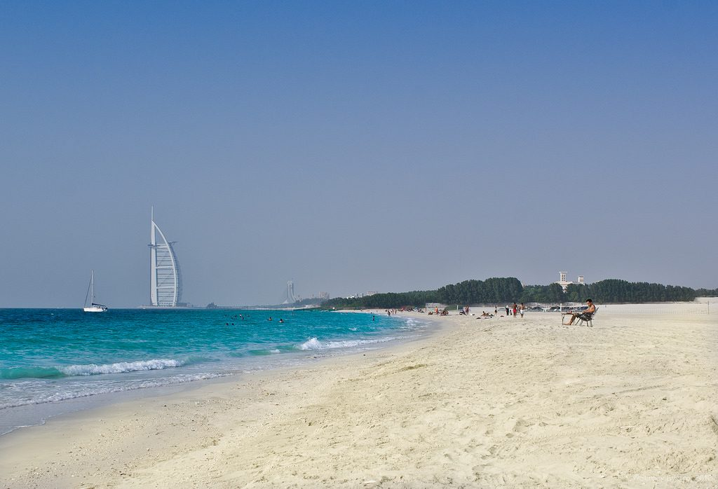 A view of the pristine white Black Palace Beach in Dubai with blue waters of the Arabian Gulf and Burj Al Arab in the background