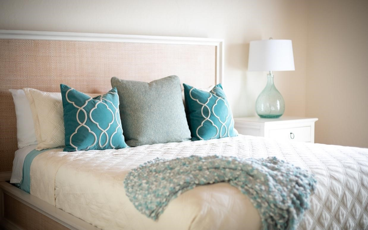 Blue cushions and throw on white bed