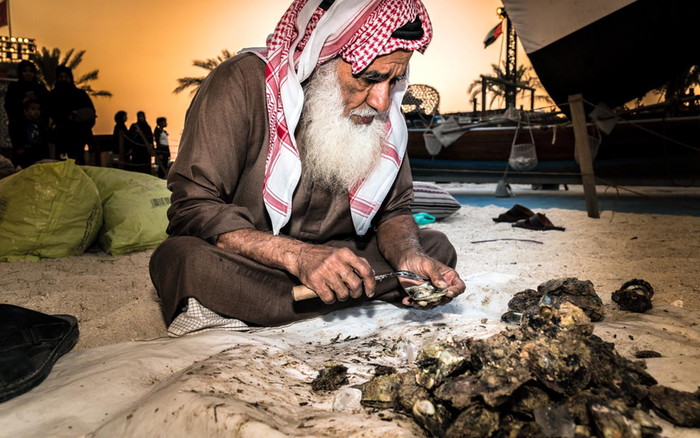 Emirati man taking out pearls from oysters