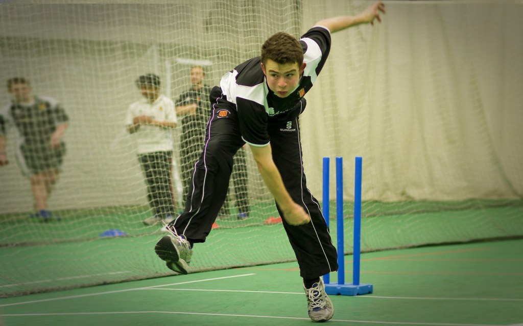 Fast bowler - a cricketer practises his technique at an indoor cricket pitch.