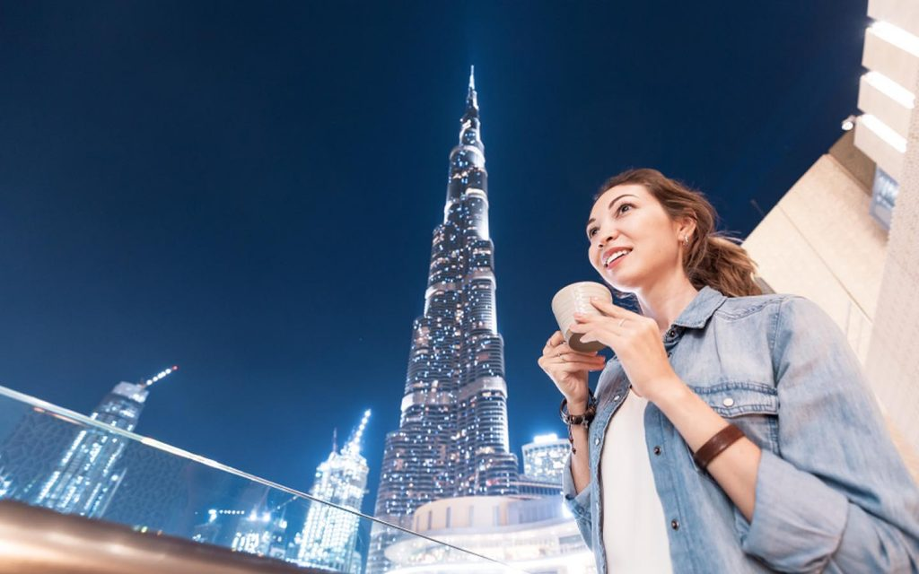 Expat woman holding a coffee cup with the  Burj Khalifa in the background