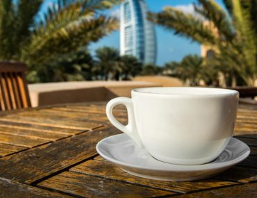 A cup of coffee on the table with the Burj Al Arab in the background