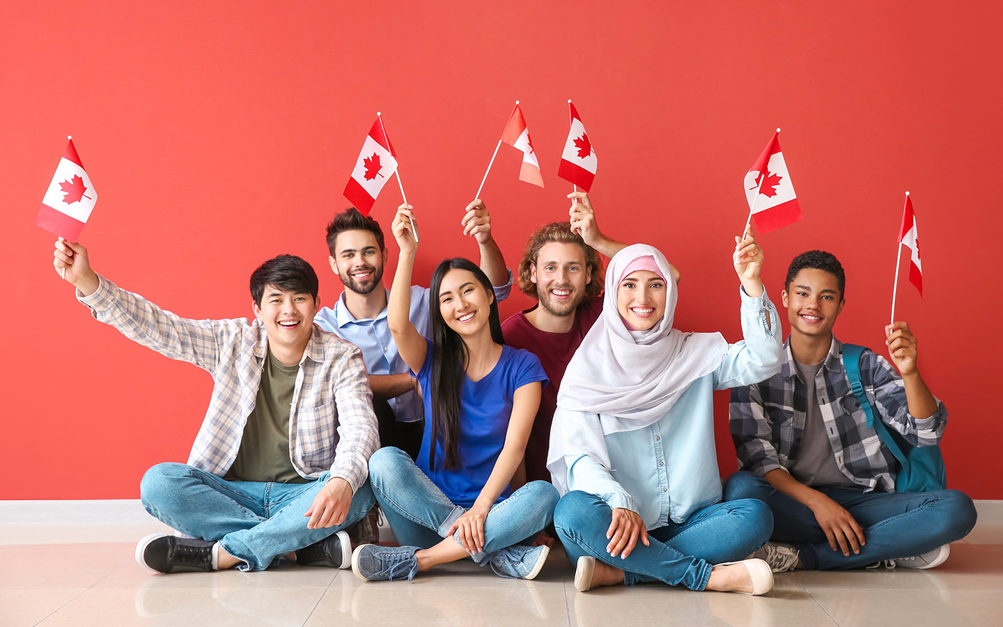 Students holding up the Canadian flag in front of a red background