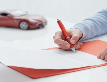 Person signing contract with one of the insurance companies in Al Ain