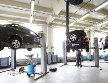 Cars lifted in a service centre as a mechanic works