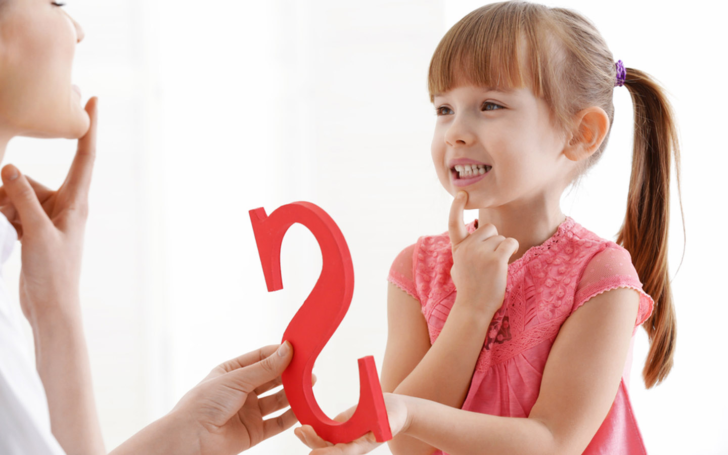 Child learning to pronounce the letter S with speech therapist