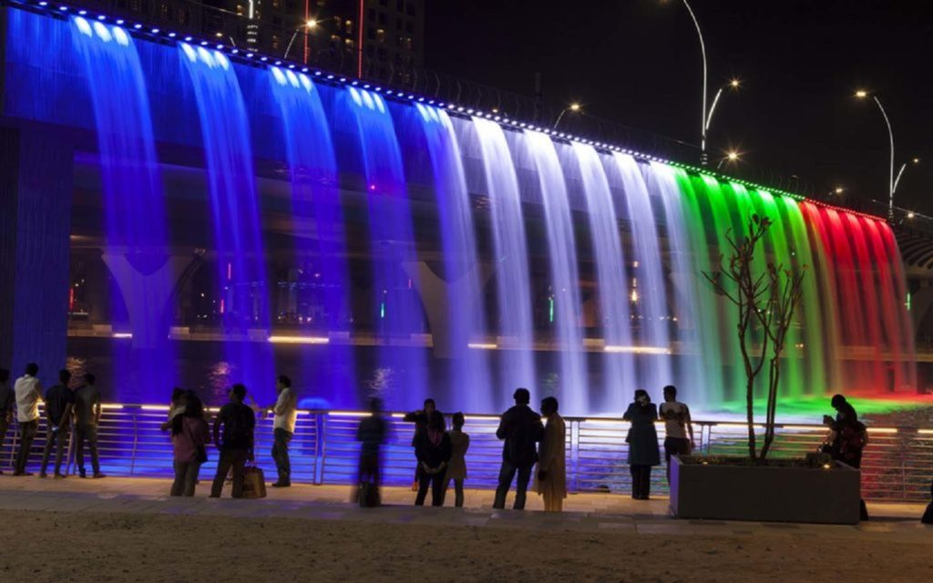People viewing the fountain coloured by UAE flag lighting