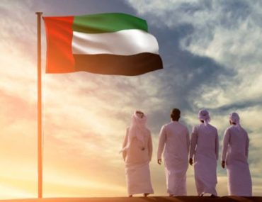 UAE nationals standing under the national flag of the UAE