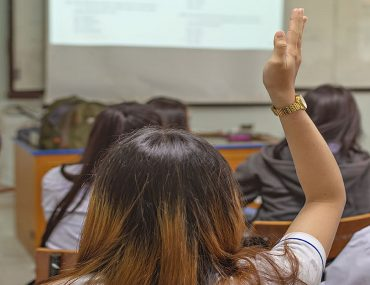 A student raises her hand to ask a question during a class in one of the schools in baniyas