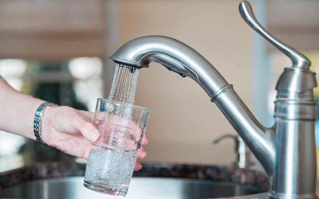 Women's hand holding a glass under an open tap