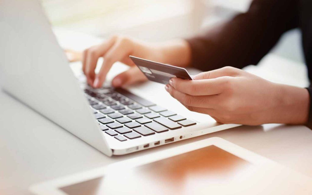 Person holding a credit card and typing on a laptop, which can be used for FEWA bill check