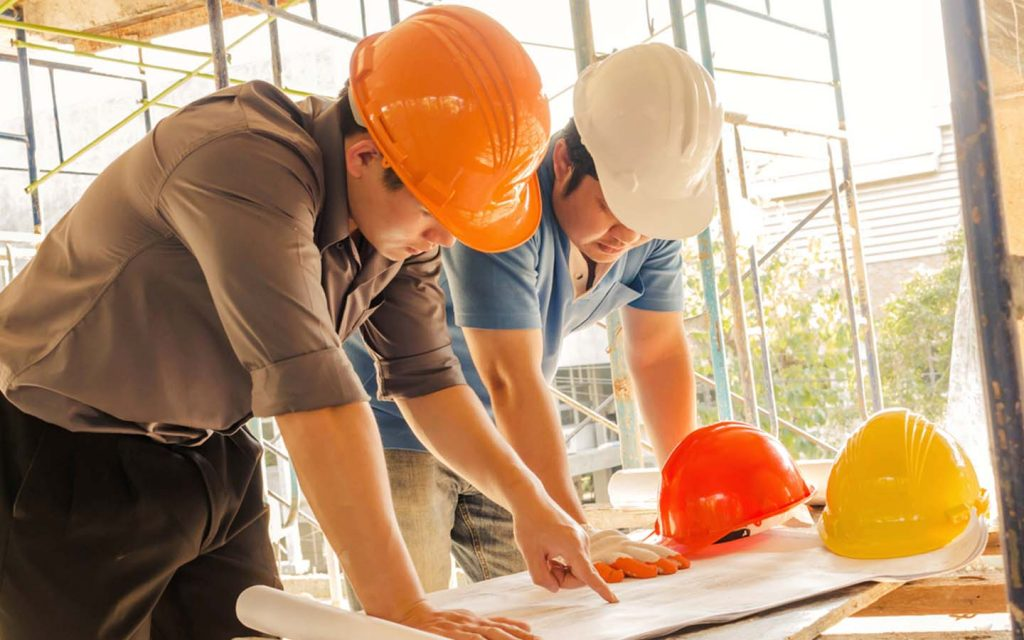 Two construction engineers looking at building plans