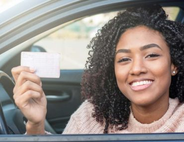 African American woman holding a driving license in car