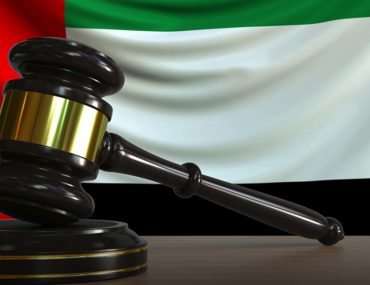 Gavel on table with UAE flag in the background